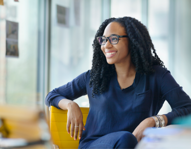 Young professional woman wearing glasses and smiling while envisioning her future