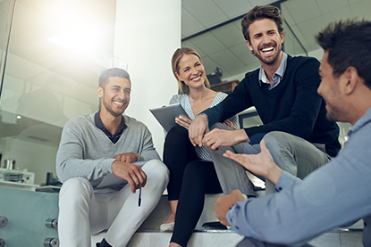 group of coworkers talking together while sitting on some stairs in an office